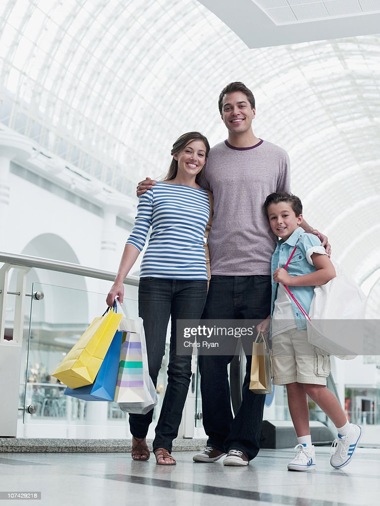 Smiling family shopping together in mall : Foto de stock
