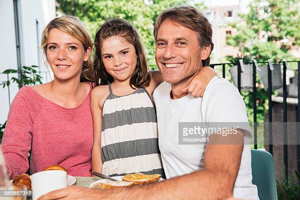 Smiling family sitting at breakfast table on balcony