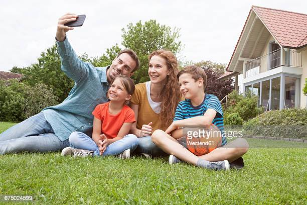 Smiling family sitting in garden taking a selfie