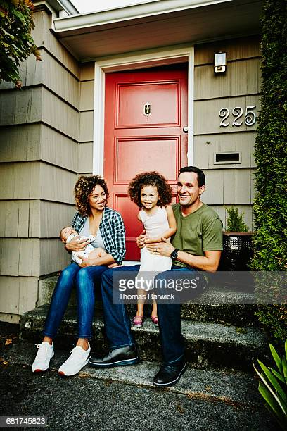 Smiling family sitting together on front porch