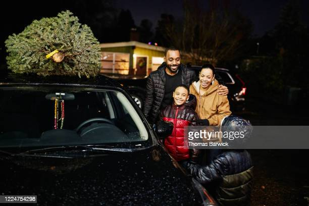 smiling family standing beside car after shopping for christmas tree - embellished jacket stock pictures, royalty-free photos & images