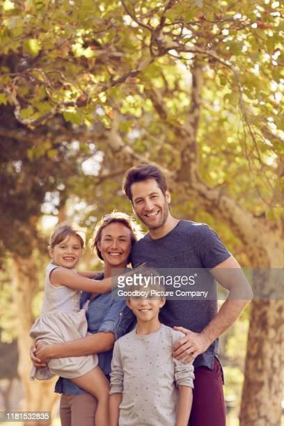 familia sonriente de pie juntos en un parque soleado - cuatro personas fotografías e imágenes de stock