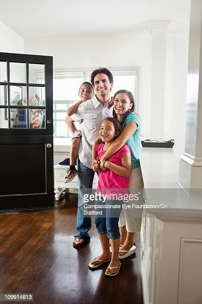 smiling family standing together in entryway