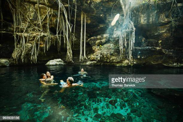 Smiling family swimming together while exploring cenote during vacation