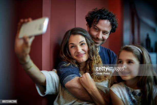 Smiling family taking a selfie at home