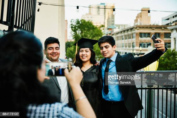 Smiling family taking photos with graduating daughter during celebration on restaurant deck