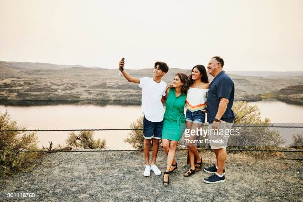 smiling family taking selfie with smart phone during summer vacation - holiday stock pictures, royalty-free photos & images