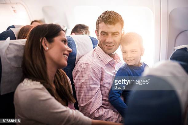 Smiling family talking while flying in the airplane.