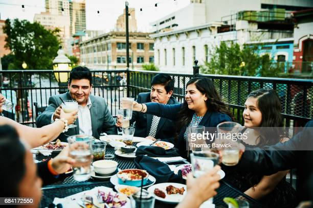 Smiling family toasting during celebration dinner on restaurant deck