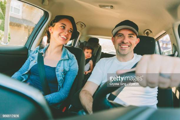 smiling family traveling in car - family driving stock photos and pictures