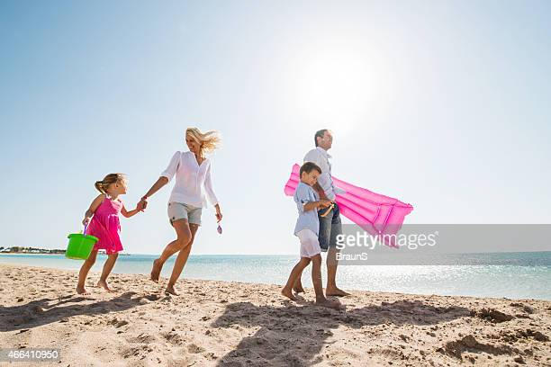 Smiling family walking on the beach during summer day.