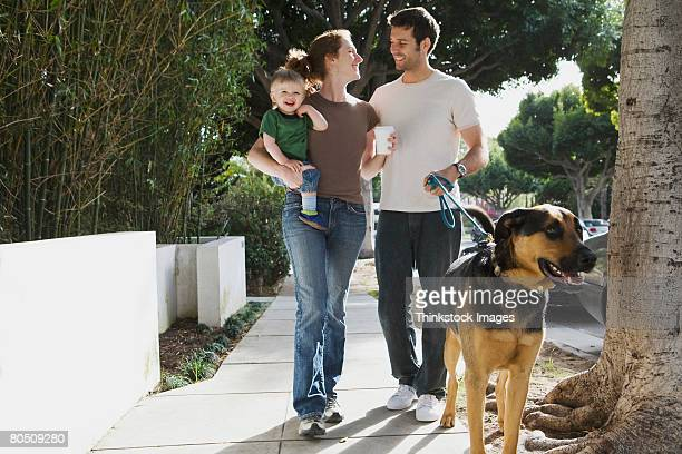 Smiling family walking with dog
