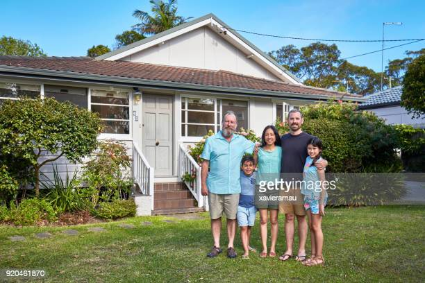 Smiling family with arms around in lawn