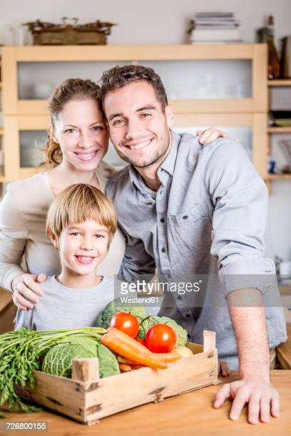 Smiling family with box of vegetables in kitchen