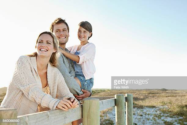 Smiling family with daughter (10-12) on beach