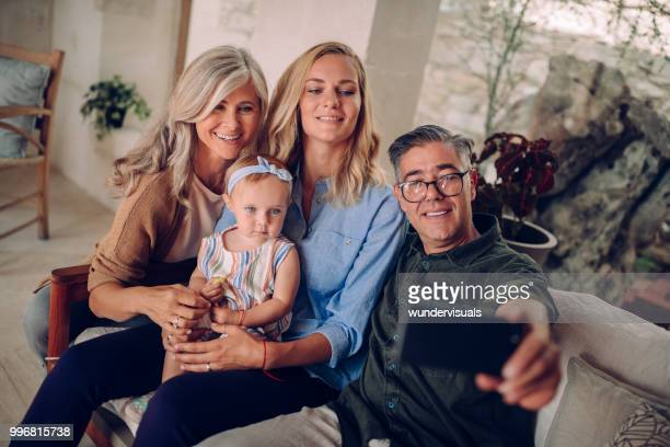 Smiling family with grandparents taking selfies on smartphone
