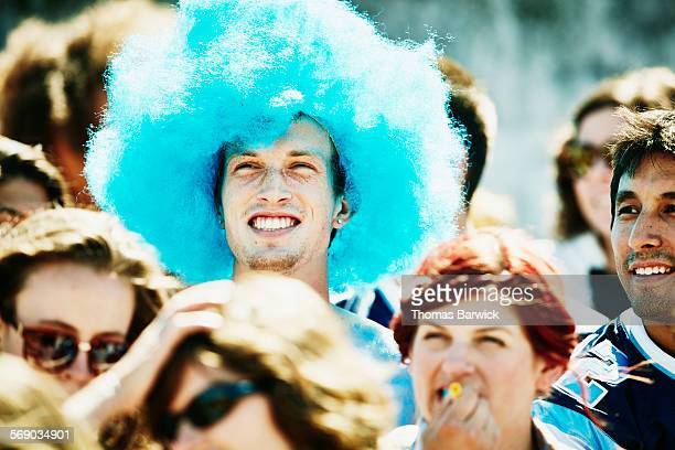 Smiling fan in blue wig watching football game
