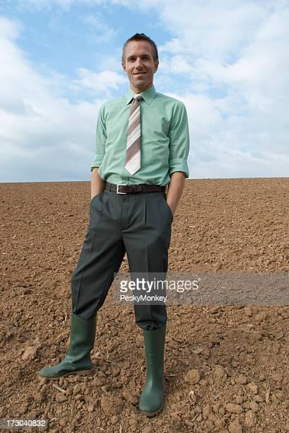 Agriculteur Homme d'affaires souriant, debout sur la terre Field