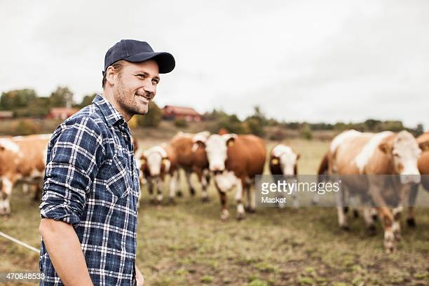 Smiling farmer looking away at field while animals grazing in background