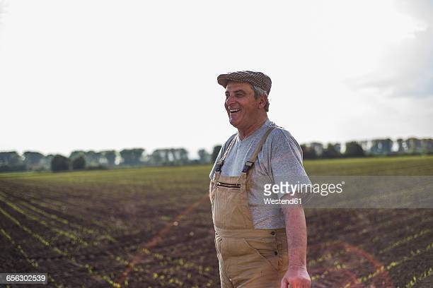 Smiling farmer standing at a field