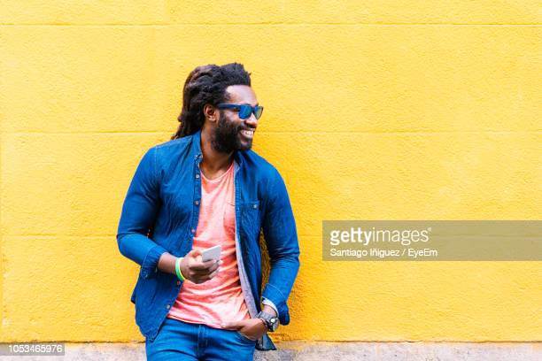 Smiling Fashionable Man Holding Smart Phone Against Wall In City