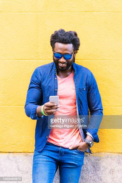 Smiling Fashionable Man Using Smart Phone Against Wall In City
