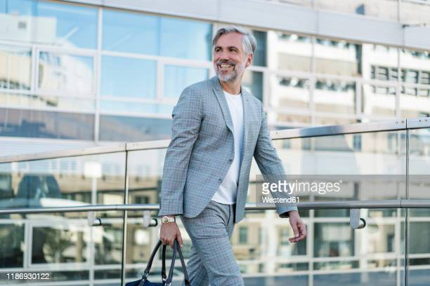 smiling fashionable mature businessman with bag on the go - menswear stock pictures, royalty-free photos & images