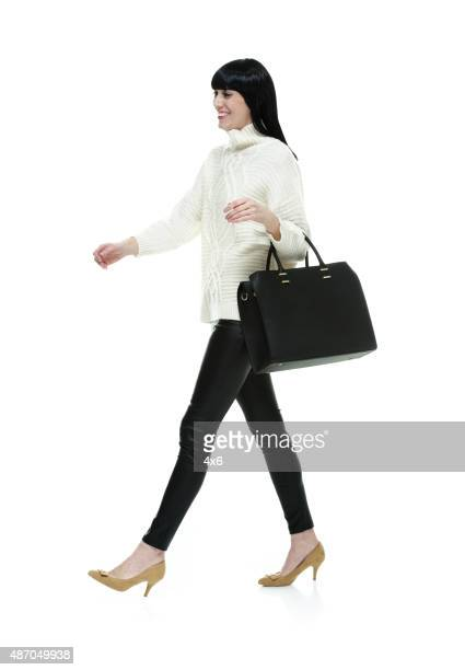 Smiling fashionable woman walking