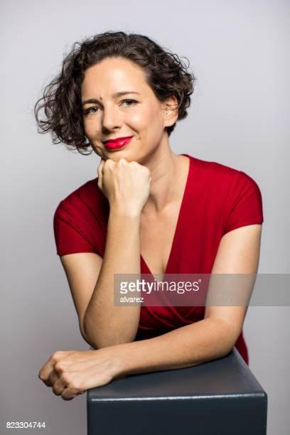 Lächelnde modische Frau mit Hand am Kinn