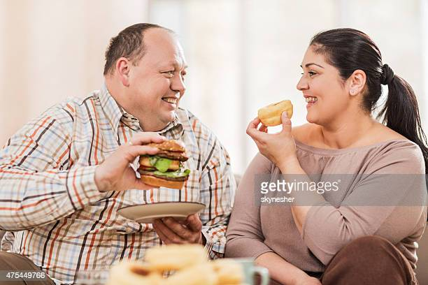Smiling fat couple eating unhealthy food at home.