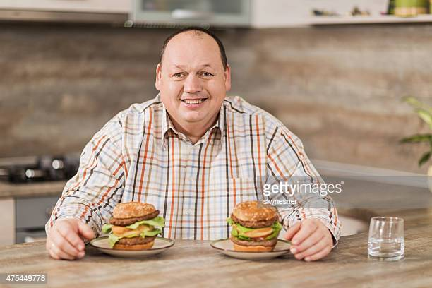 Smiling fat man sitting in front of two hamburgers.
