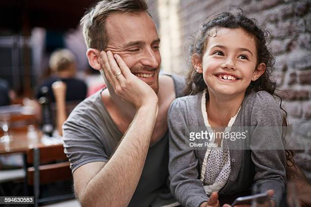 Smiling father and daughter in a restaurant