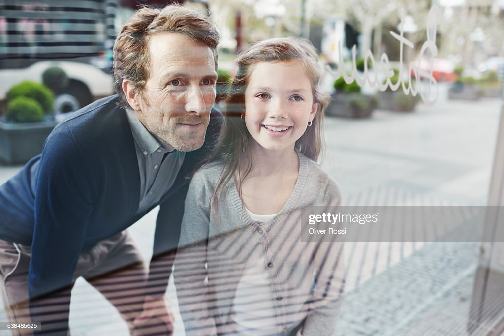 Smiling father and daughter looking at shop window : Stock Photo