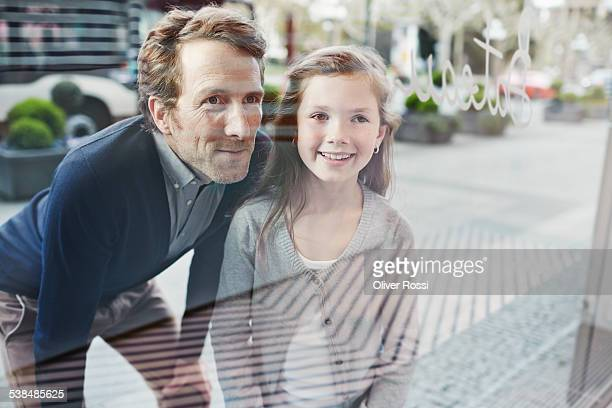 Smiling father and daughter looking at shop window