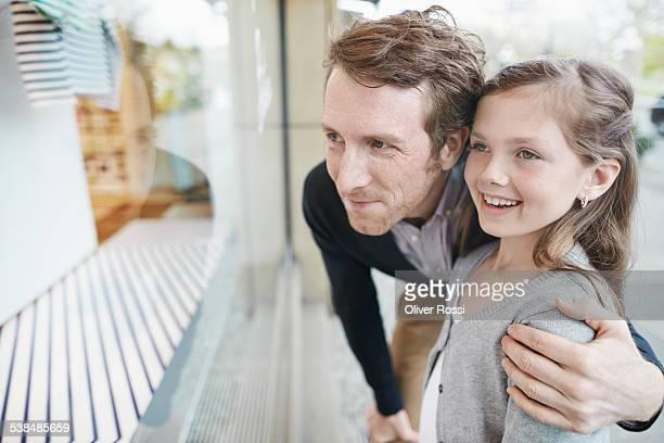 smiling father and daughter looking at shop window - hand auf der schulter stock-fotos und bilder