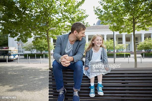 smiling father and daughter on bench - sitzen stock-fotos und bilder