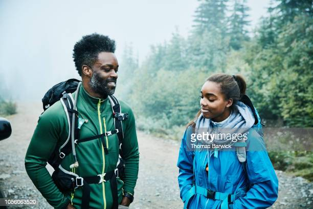 Smiling father and daughter preparing for early morning hike