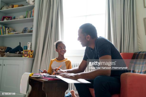 smiling father and daughter sitting at home - homeschool stock photos and pictures
