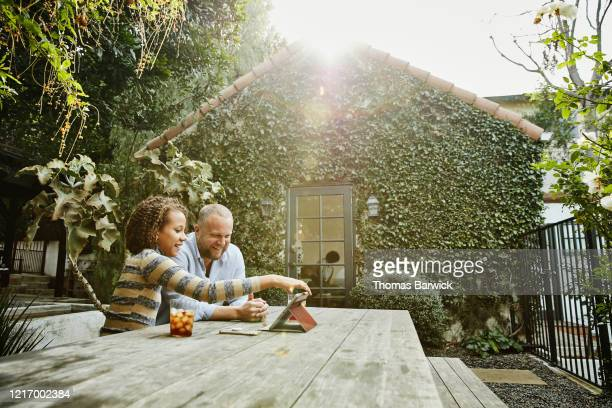 smiling father and daughter watching video on digital tablet in backyard - daughter stock pictures, royalty-free photos & images