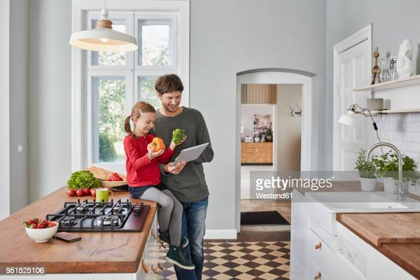 smiling father and daughter with bell pepper and tablet in kitchen - genderblend stock-fotos und bilder