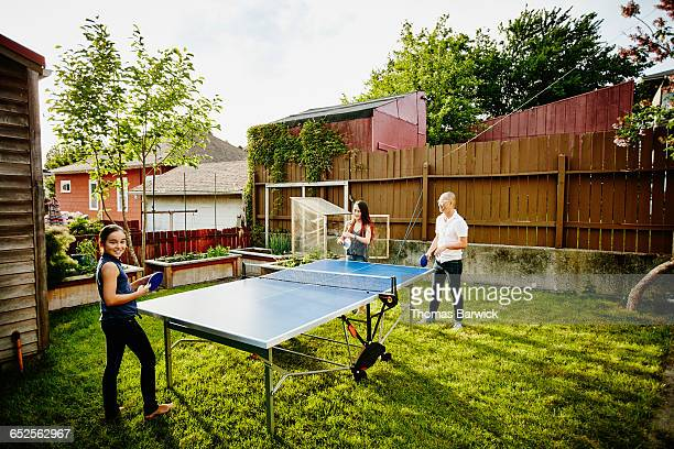 Smiling father and daughters playing ping pong