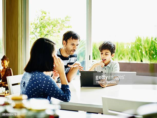 Smiling father and son looking at digital tablet