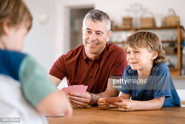 Smiling father and son playing cards at home