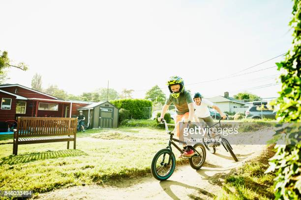 Smiling father and son racing BMX bikes on dirt track in backyard on summer afternoon