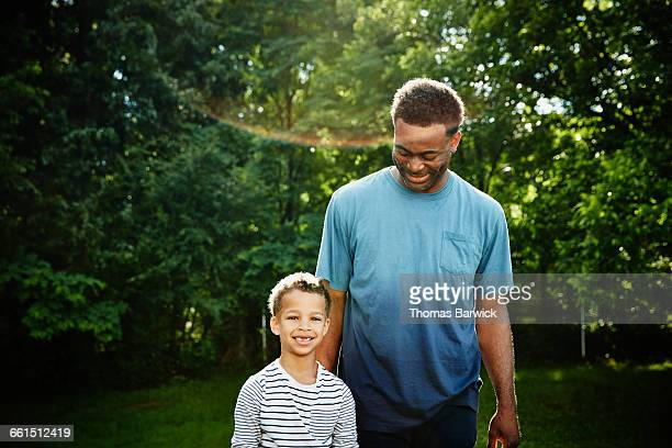 Smiling father and son standing outside