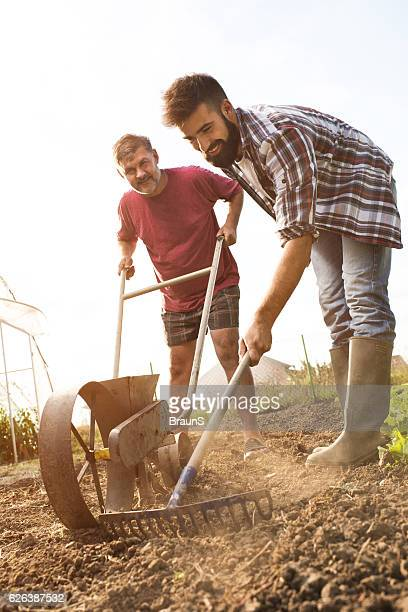 Smiling father and son working together on a field.