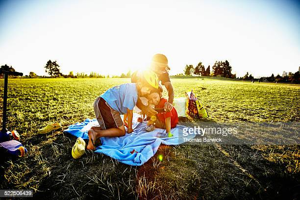 smiling father and sons looking at smartphone - leanintogether stock pictures, royalty-free photos & images
