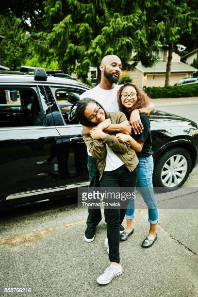 Smiling father and twin daughters embracing on sidewalk in front of home