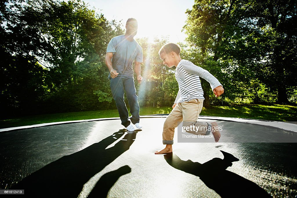 Smiling father and young son jumping on trampoline : Stock Photo