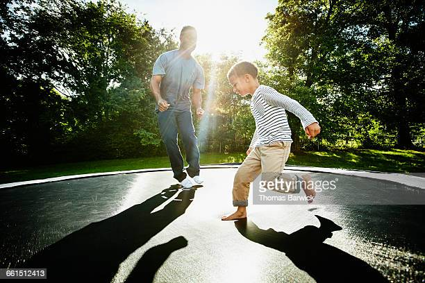 Smiling father and young son jumping on trampoline